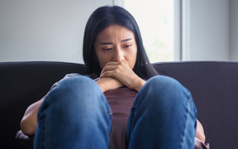 picture of a woman thinking on the couch after being blamed by a narcissist
